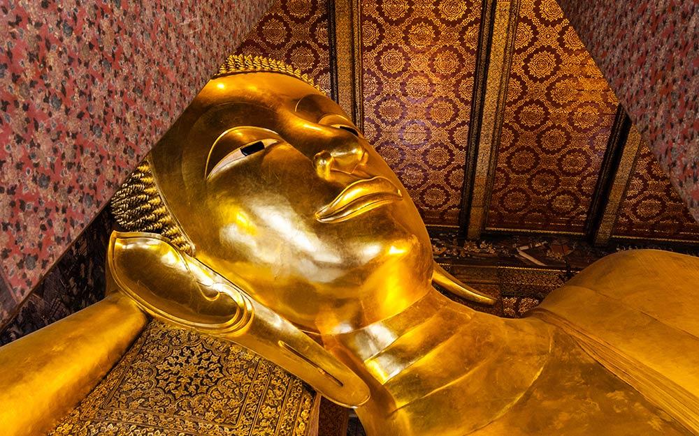 Il volto dell'imponente statua del Buddha sdraiato del Wat Pho. Il colosso misura 46 m in lunghezza e 15 m in altezza. Fu costruito in occasione della ristrutturazione di Rama III. Il corpo è rivestito d'oro, gli occhi e i piedi sono decorati con madreperla, e sulle piante dei piedi sono raffigurate 108 scene augurali abbellite da conchiglie in stile cinese e indiano.