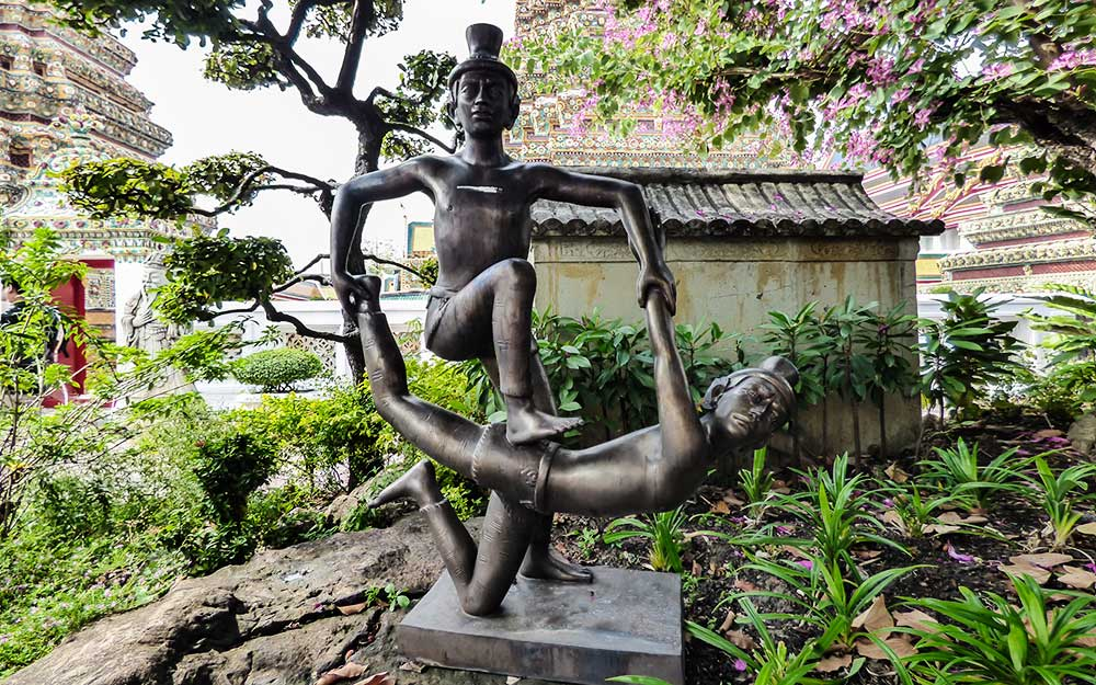 """Statua che raffigura una posizione di stretching assistito del massaggio thai delle origini. Un curioso """"libro di testo"""" presente nel giardino del Wat Pho. La prima scuola di massaggio thai."""