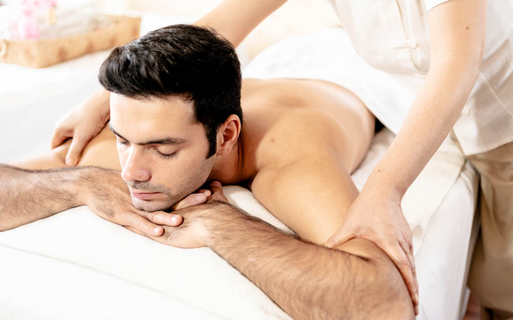 Uomo stressato dal lavoro che trae beneficio dal massaggio thailandese